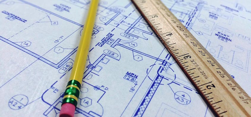 A pencil, ruler, and set of blueprints