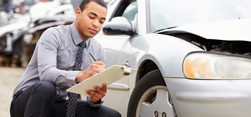 An insurance agent inspecting the damages to a car